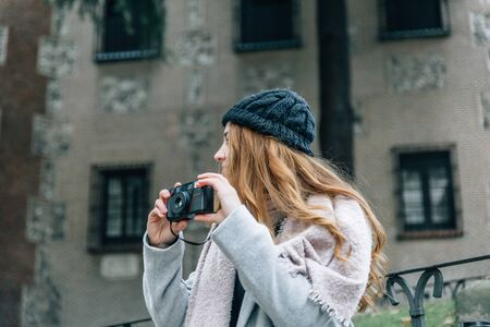 Blonde girl with a hat holds in her hands an old vintage camera on a city street on a cold autumn day