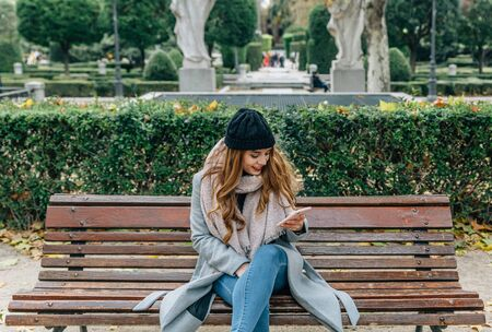 Caucasian blonde girl with coat, scarf and hat, checks her smartphone while sitting on a park bench in a city