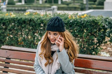 Pretty blonde woman smiling and happy, speaks on the mobile phone while sitting on the bench of a park on a winter day
