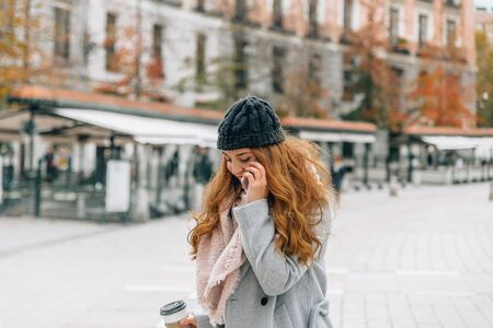 Young blonde woman with winter clothes speaks on the mobile phone while carrying a cup of coffee in the other hand walking through the city