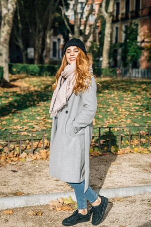 Blonde girl with dark blue cap gray coat and pink scarf smiles as she walks leisurely through a park
