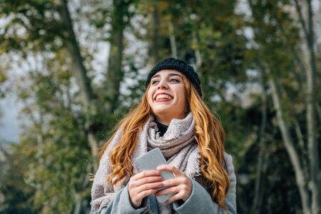 Beautiful caucasian blonde girl with wide smile in a park with a smartphone on a cold autumn day in Europe