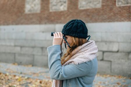 Blonde caucasian woman watches something with binoculars while on a city street on a cold winter day