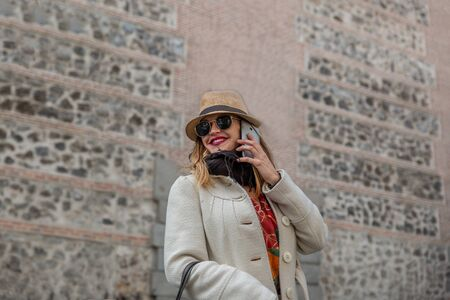 Very attractive blonde woman smiling with coat and black glasses speaks on her mobile phone by a city street