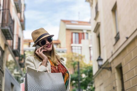 Attractive smiling blonde girl speaks on her mobile phone while walking with shopping bags through a city