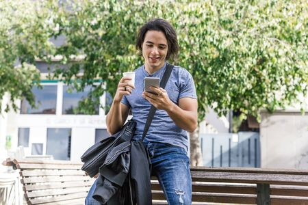 Long haired caucasian boy with blue casual clothes smiles as he looks at his cell phone sitting on a park bench