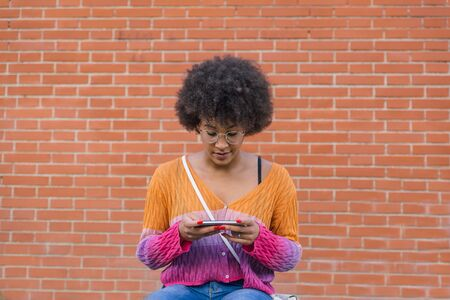 Very pretty afro style girl in spring clothes looks concentrated at her mobile phone sitting in front of an orange brick wall 写真素材 - 143280348