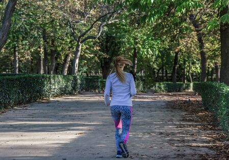 Back view of a female runner running in a park on a spring day with a green nature background 免版税图像