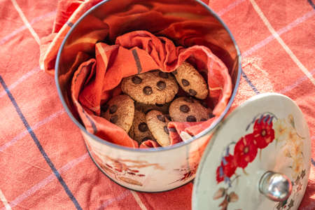 Metal jar with cookies inside on a table with red tablecloth Archivio Fotografico
