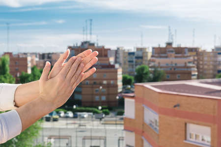 Man hands clapping from the balcony of his house with the city in the background