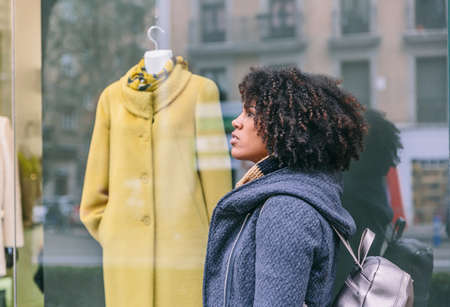 Attractive afro hair woman with coat walks in front of a stylish clothing store Archivio Fotografico