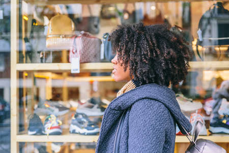 Attractive African American girl with coat and elegantly walks in front of a shop window