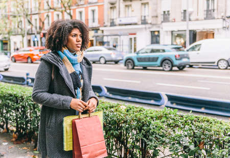 Afro style girl goes shopping in a city and carries colorful bags