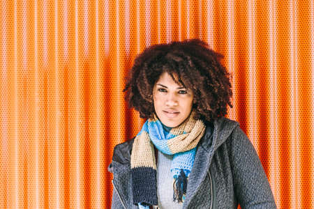 Gorgeous African American style woman with gray coat in front of an orange wall