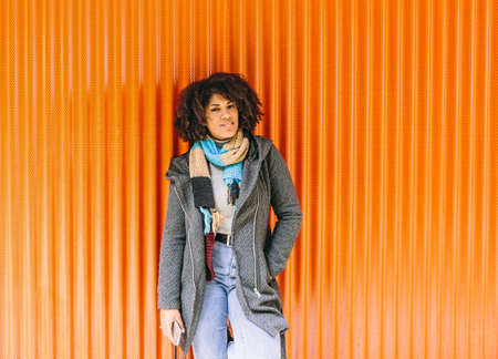 African American style girl with gray coat and jeans in front of an orange wall
