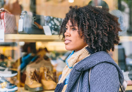 Thoughtful and elegant afro hair woman in front of a large shop window
