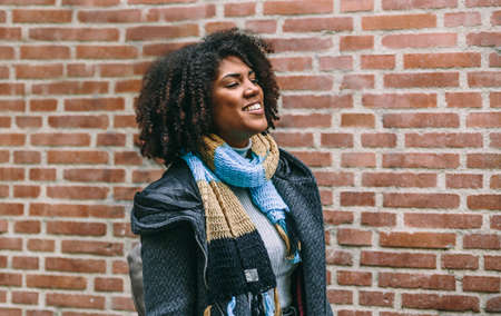 Happy brunette woman in coat and scarf walks smiling in front of a brick building