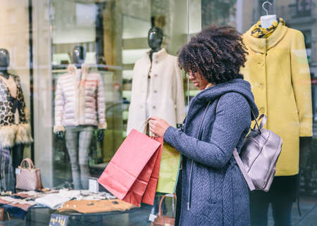 Afro hair woman in elegant gray coat looks at a bags on a shopping ans cold day