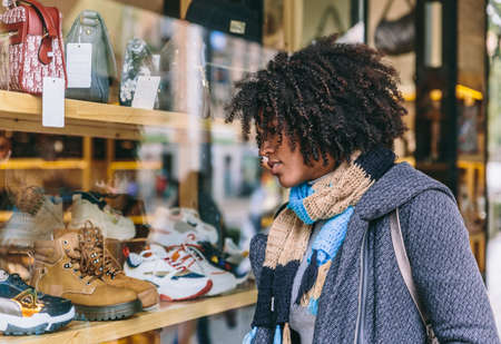 Attractive stylish afro hair girl looks at a shop window on a shopping day