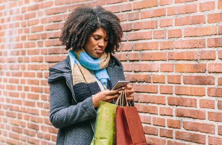 Stylish afro hair woman with bags in hand looks at her mobile phone on a street