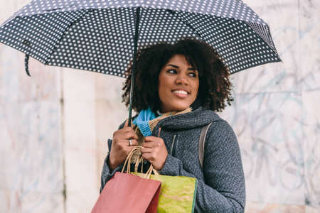 Beautiful afro styled brunette woman smiles with an umbrella and some bags in front of a gray wall Archivio Fotografico