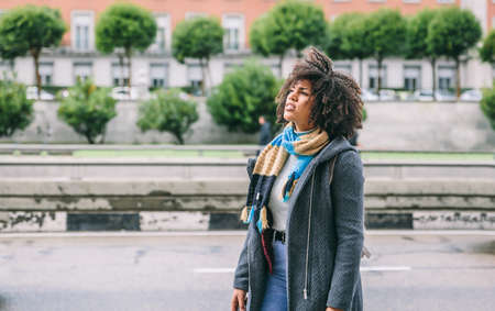 Dark skinned woman with afro hair on the street of a city on a cold day Archivio Fotografico