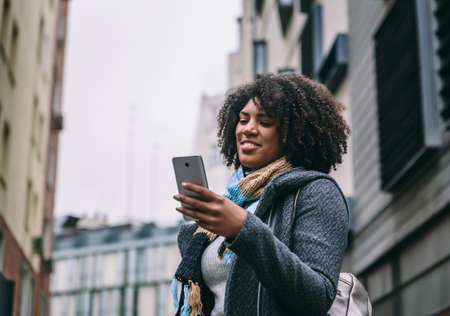 Attractive brunette girl with afro hair smiles while looking at mobile phone on the street in winter Archivio Fotografico