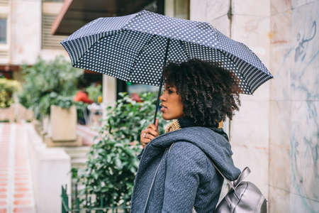 Attractive brunette with afro hair with an umbrella and a coat in front of a building