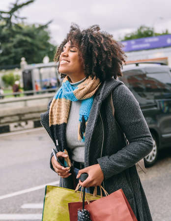 Afro-haired woman smiles very happily down the street a cold day