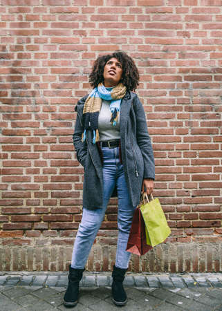Afro haired brunette woman dressed in coat and scarf, carries some shopping bags