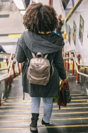 Afro hair woman with coat and backpack walking down some stairs inside a building