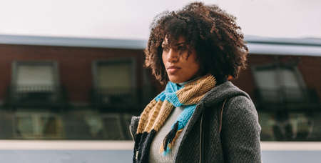 Brunette woman who has afro hair stares absorbed in a street