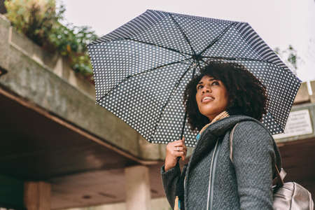 Brunette woman in afro style smiles carrying an umbrella in a cloudy day