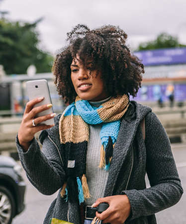 Brunette woman with afro hair and coat looks happily at her mobile phone in the street