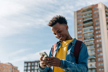 Happy brunette boy with afro hair smiles looking at his mobile phone Archivio Fotografico
