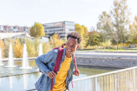 Young African American man smiles in a wide area of the city on a summer day