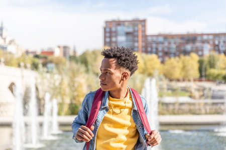 Attractive black guy with his backpack looks to the side in the city in summer