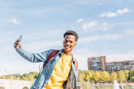Attractive African American man smiles in front of his smartphone in the street on a summer day Archivio Fotografico