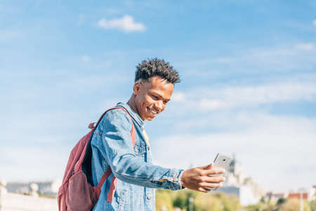 Happy and smiling boy with dark skin and afro hair looks at his mobile phone in a sunny day Archivio Fotografico