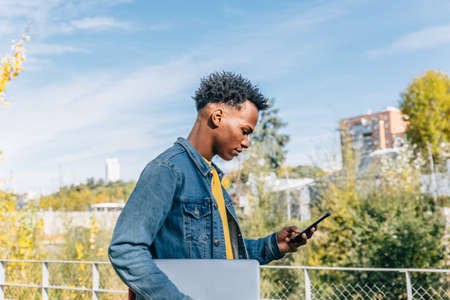 Young boy with afro hair looks worriedly at his mobile phone in a city in a sunny day