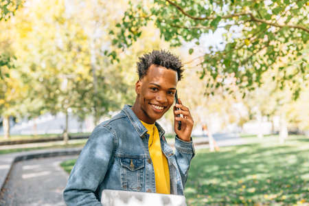 Smiling young boy with perfect teeth speaks on his smartphone in a park