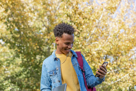 Happy guy in casual clothes looks at his phone on an autumn day