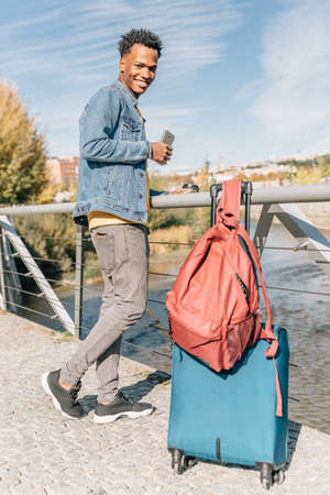 Traveler boy rests with his suitcase and backpack next to a river in a summer day Archivio Fotografico