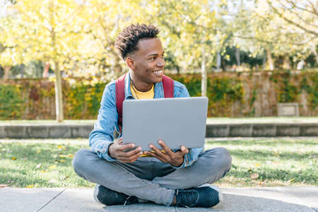 African American digital nomad man works with his laptop sitting in a park