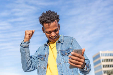 Optimistic man looks at his mobile phone and raises his fist on a sunny day Archivio Fotografico