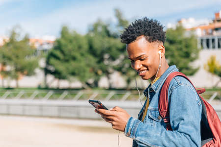 Happy guy with afro hair looks smiling at his mobile phone on a summer day