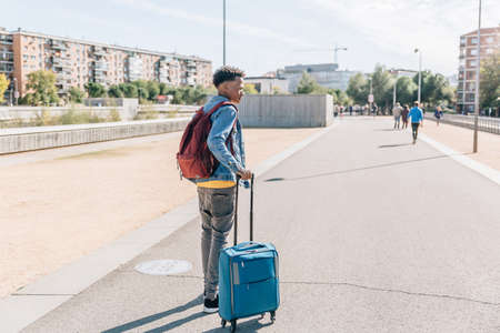 Traveler with his suitcases and backpack walks through a city in summer Archivio Fotografico
