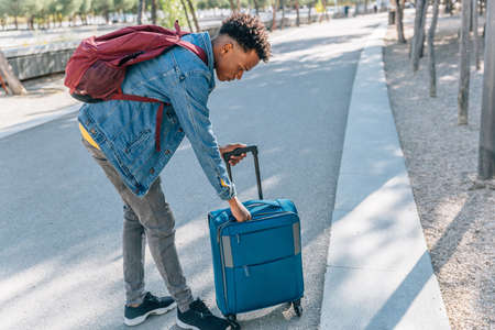Traveler with afro hair checks his suitcase in the middle of a park in a city