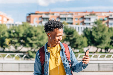 Handsome boy with dark skin smiles looking at his mobile phone and listening to music Archivio Fotografico