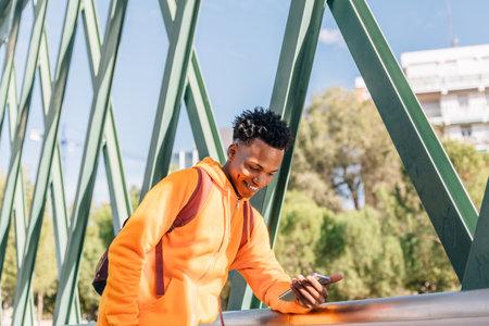 Happy man in casual wear smiles looking at his mobile phone on a metal bridge Archivio Fotografico